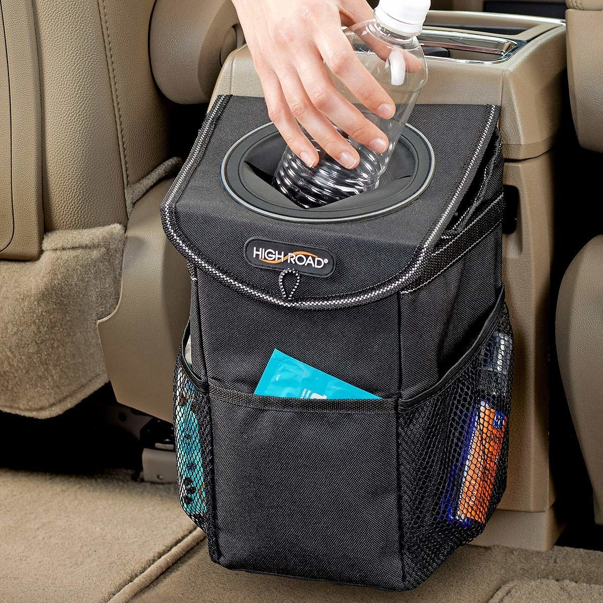 A small black trash can hooked to the back of a car console with pockets and a little hole for depositing trash