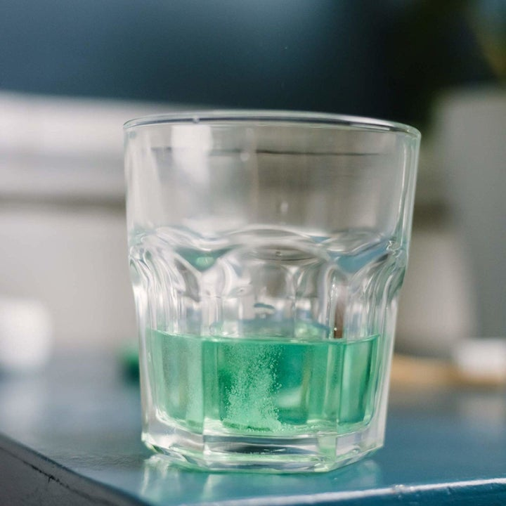 glass with green mouth wash in it