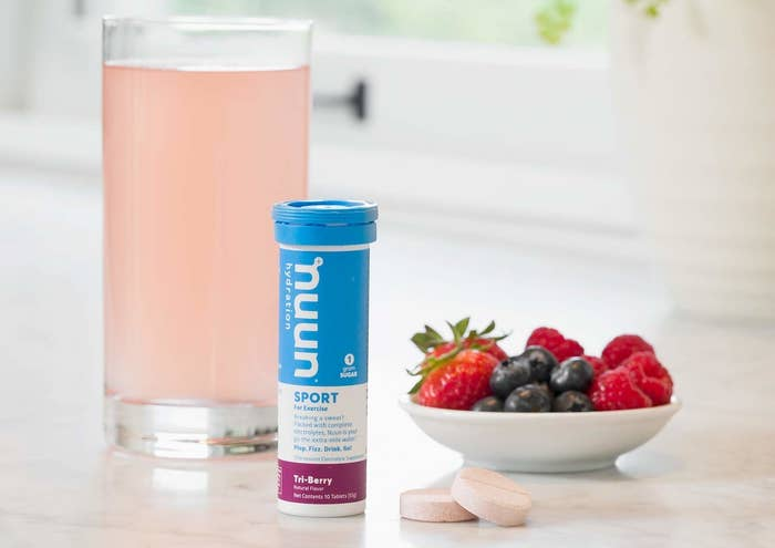 tube of tablets next to pink drink