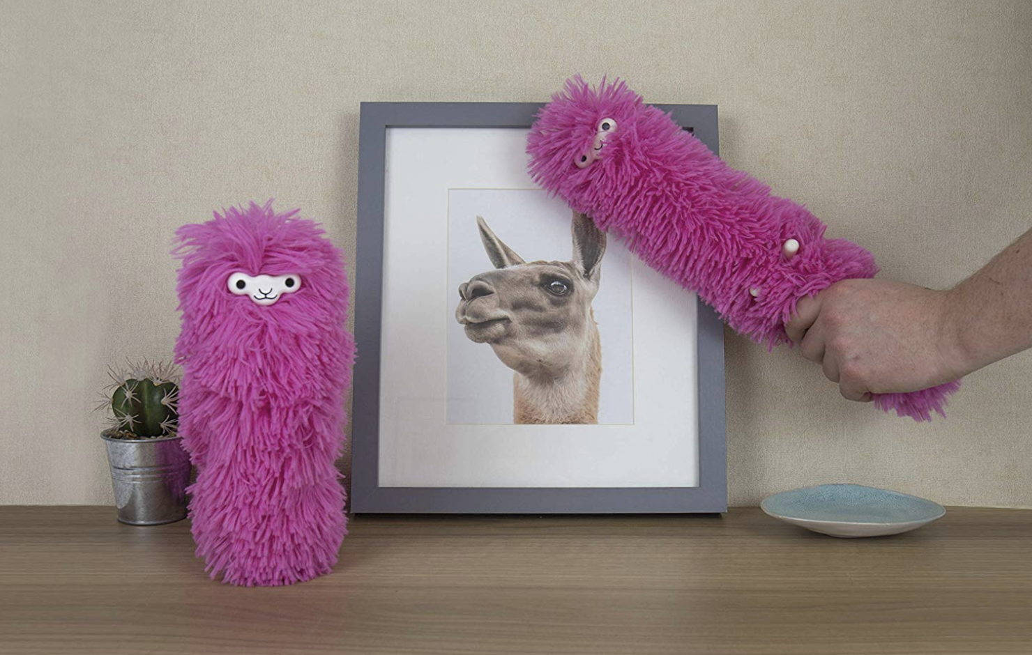 Pink llama-shaped dusters in front of llama art print on top of a table