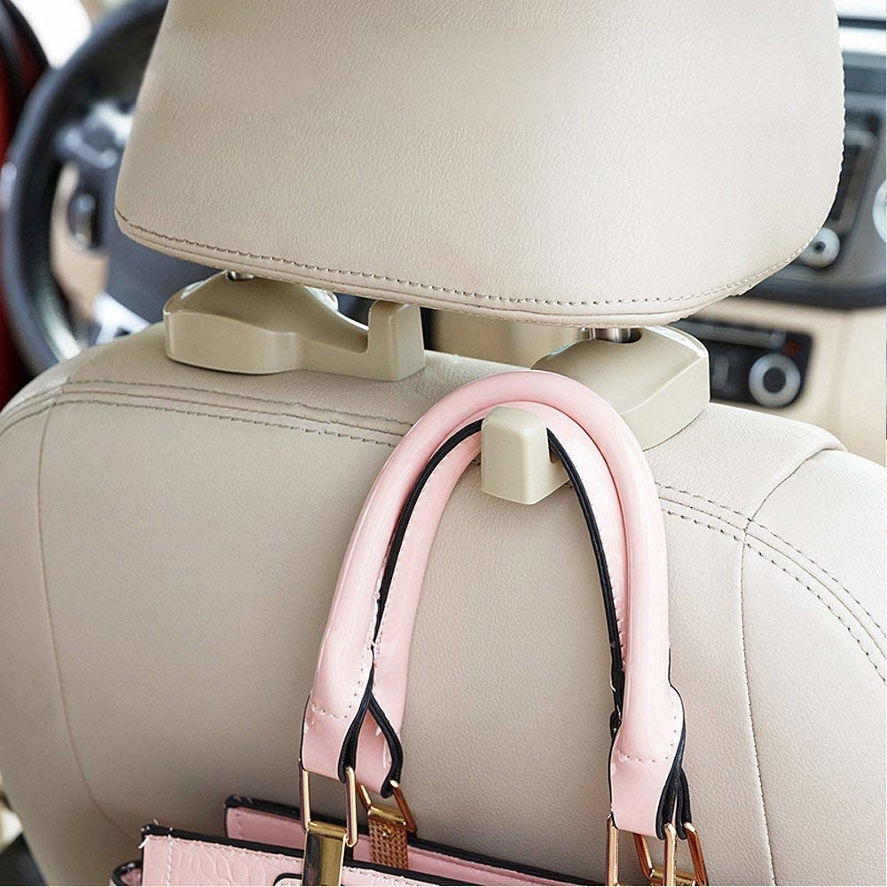 Purse hooked to the back of a car seat with installed beige hook