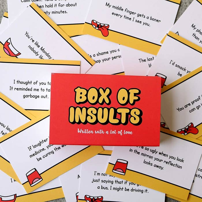 A box of insults kept on top of various cards with insults on them.