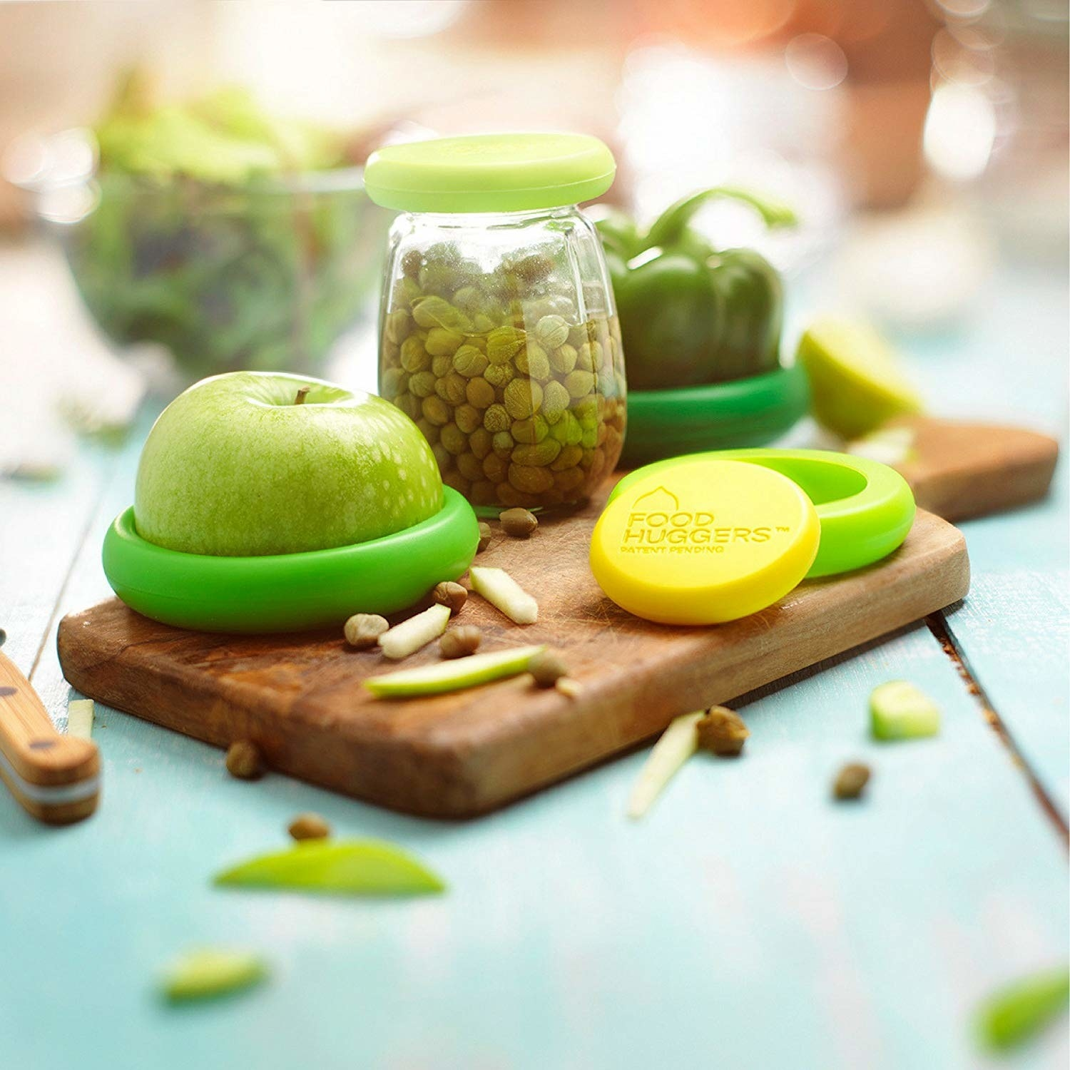 A jar, an apple, and a pepper covered with food huggers
