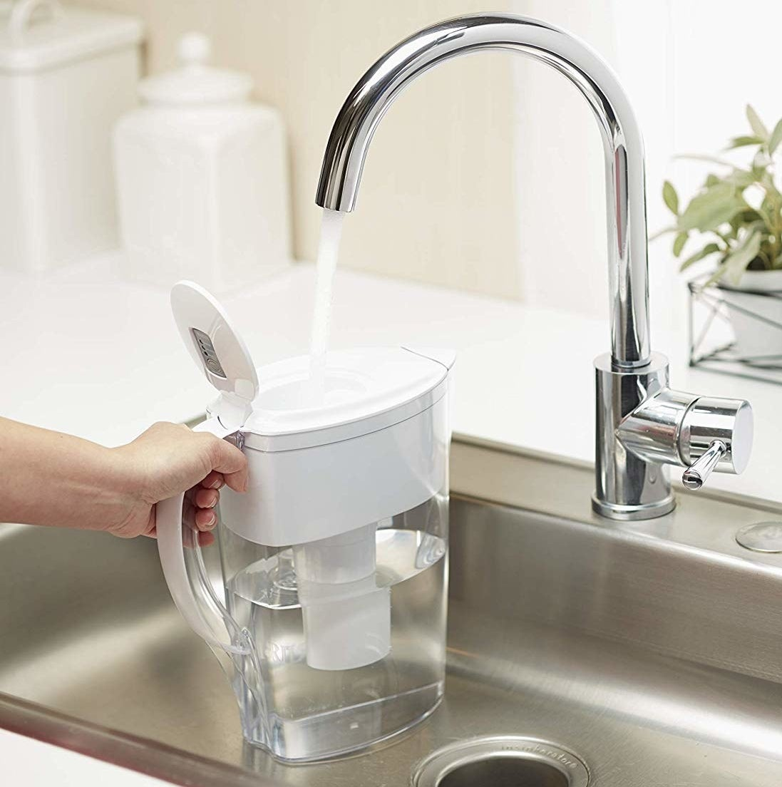 A person filling up their Brita picture with water