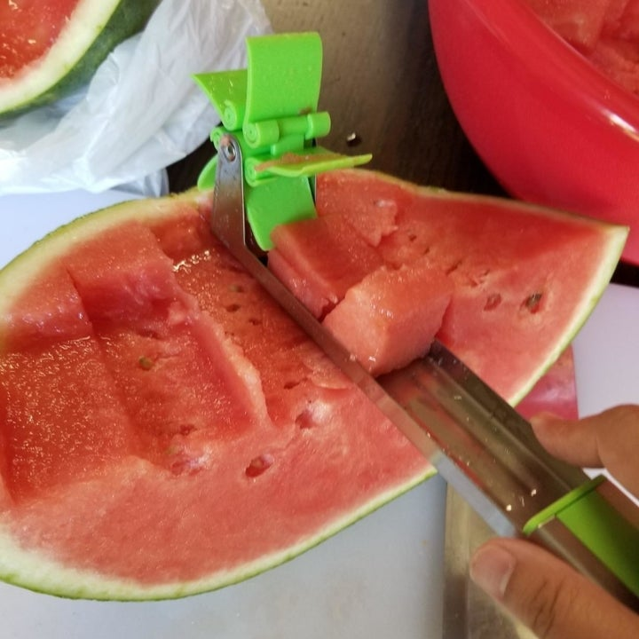 the same reviewer lifting out a scoop of fruit out of the watermelon using the utensil