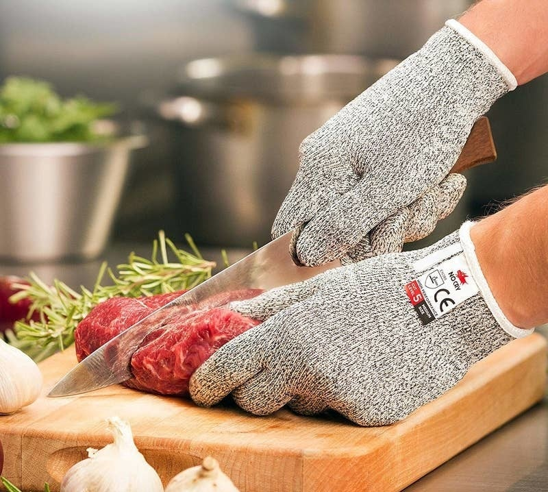 a person wearing the gray gloves while cutting a piece of raw meat