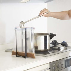 a person using the tower to keep a bag open as they ladle soup into it