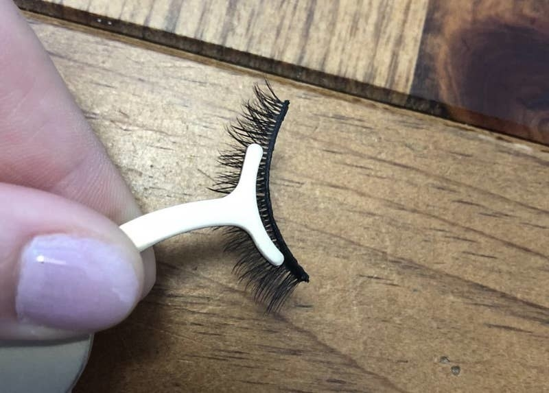 person holing the applicator with a false eyelash on it
