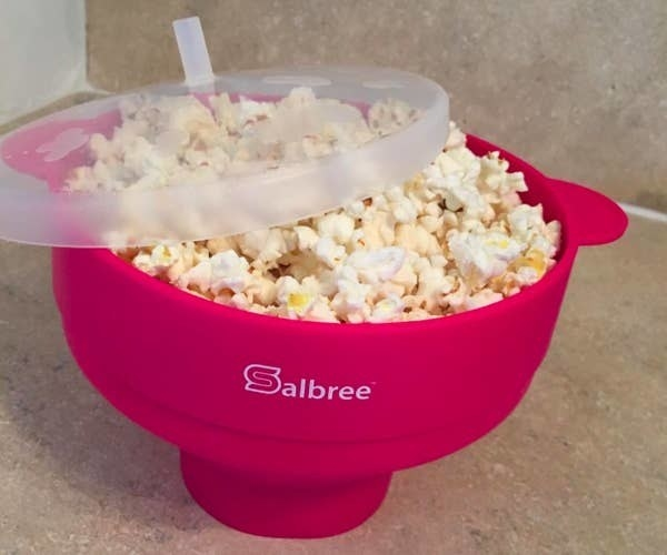 a reviewer photo of the popcorn bowl in magenta filled with popcorn