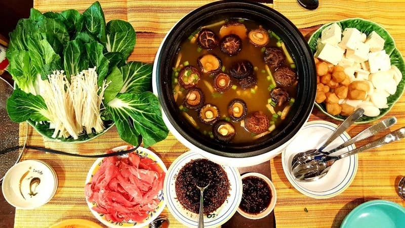 the super pot on a stove surrounded by different types of food and spices