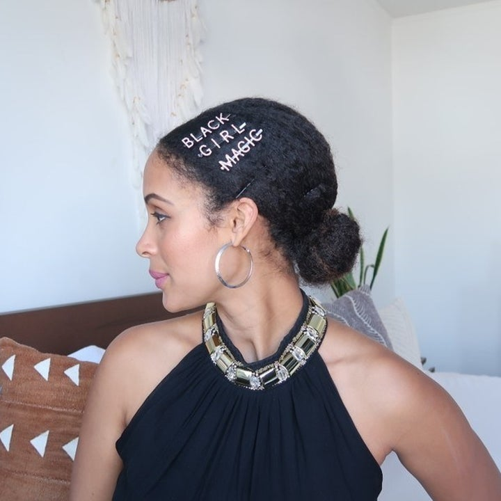 """person of color with curly hair wearing hair in low bun with the clips """"BLACK"""" """"GIRL"""" and """"MAGIC"""" pinned into hair"""