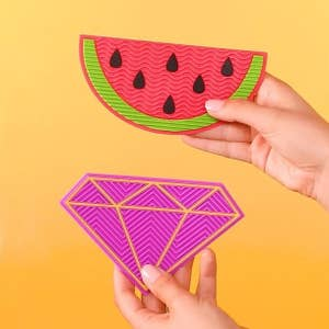 Hands holding up the palm-sized, textured mats in the watermelon and diamond shapes