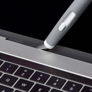 Closeup of the brush in the crevice of a laptop, illustrating how it can clean it