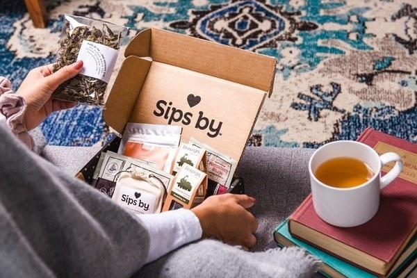 model opens box filled with various teas