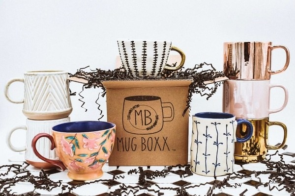 A variety of mugs with floral print, chevron designs, and gold finishes