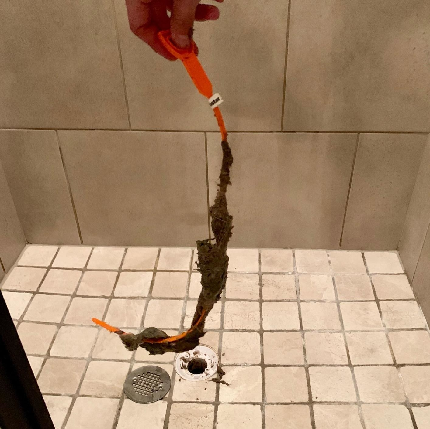 A reviewer showing the drain snake covered in gunk from their drain