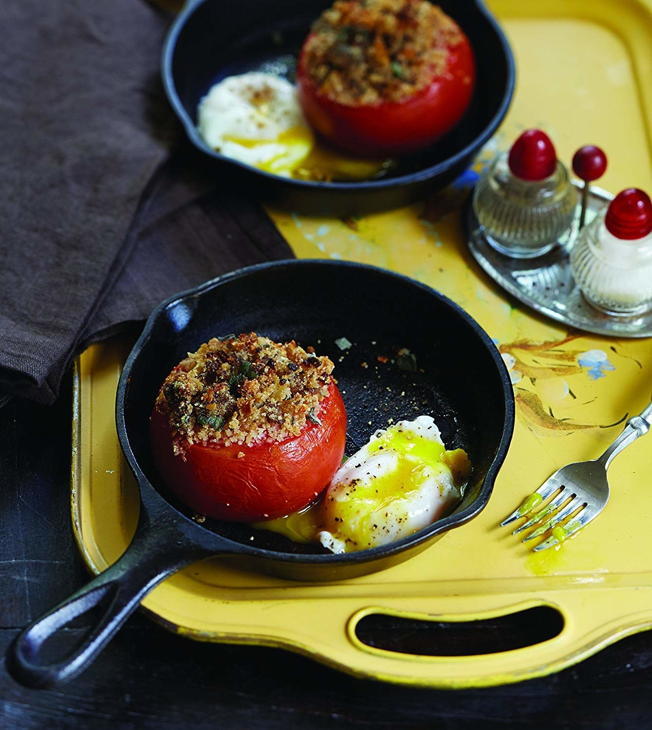 A small skillet that is holding a stuffed tomato and a poached egg