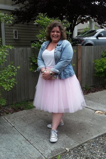 reviewer wearing the skirt in pink with sneakers and a denim jacket