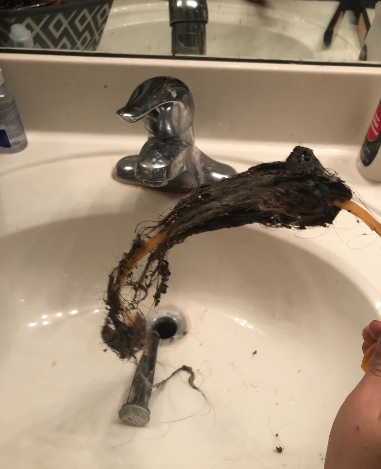 a reviewer's drain snake covered in hair after being used to unclog a bathroom sink