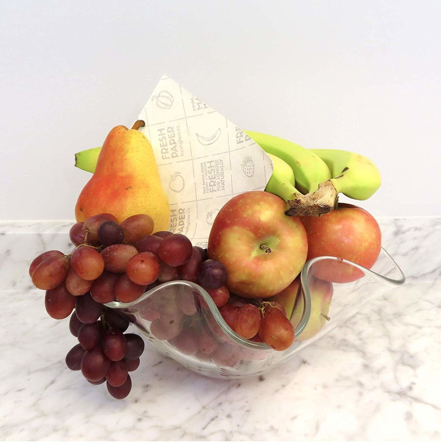 a glass bowl containing various fruits and a fenugreek-infused sheet