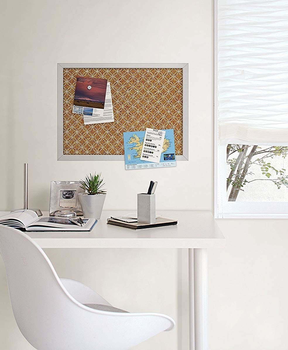 A cork board mounted on a wall above a clean desk