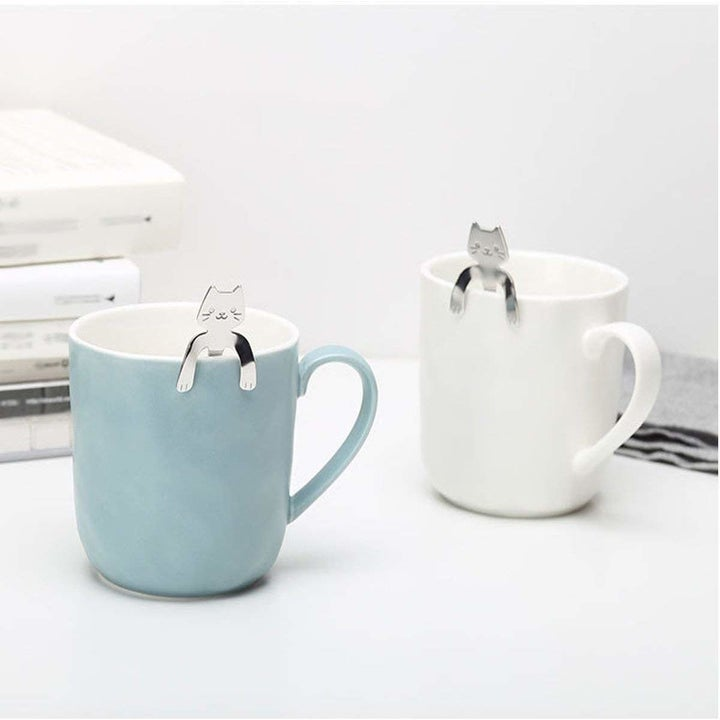Silver cat spoons hanging on the rim of a mug by their paws
