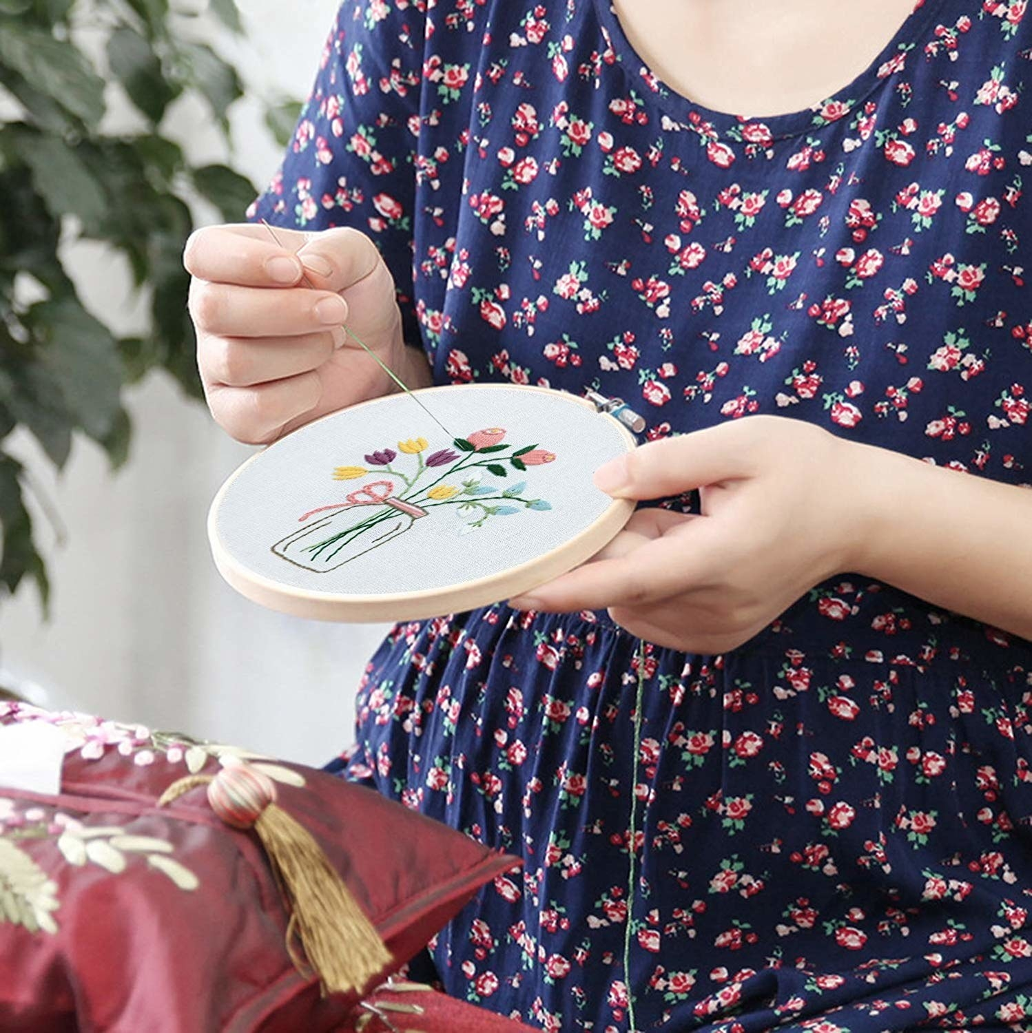 Model embroidering flowers into a hoop