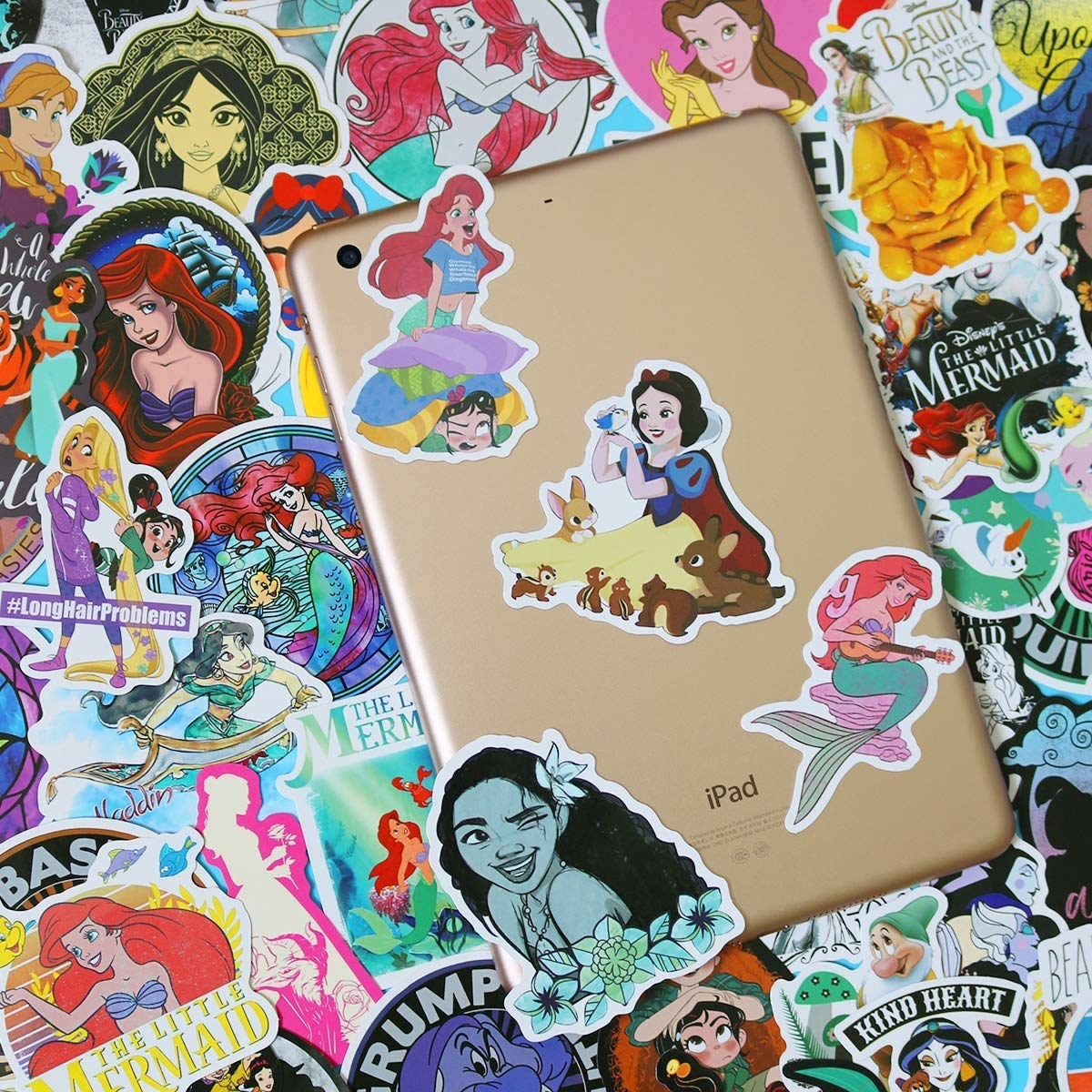 """A whole mess of Disney princess stickers in different styles on a table, from classically animated to more """"modern"""" versions, with an iPad with some stickers on it resting on top"""