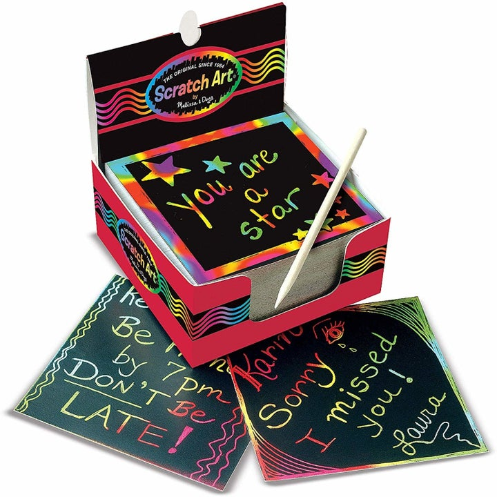 A pile of black note cards with rainbow messaged etched into them
