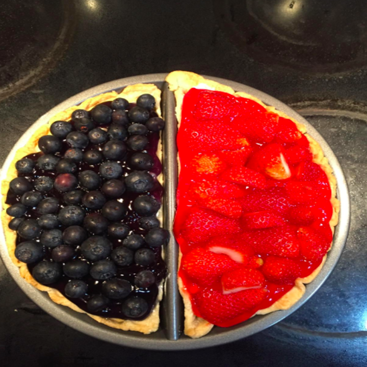 a blueberry pie in one half of the pan, and a strawberry pie in the other half
