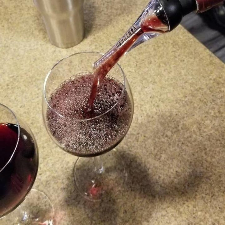 a reviewer photo of the aerator being used to pour wine into a glass