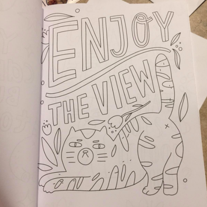 the book opened to a page that reads enjoy the view with a cat's butt in the air