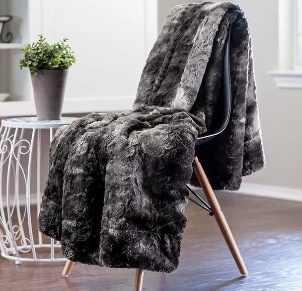 the gray faux fur blanket hanging over a chair