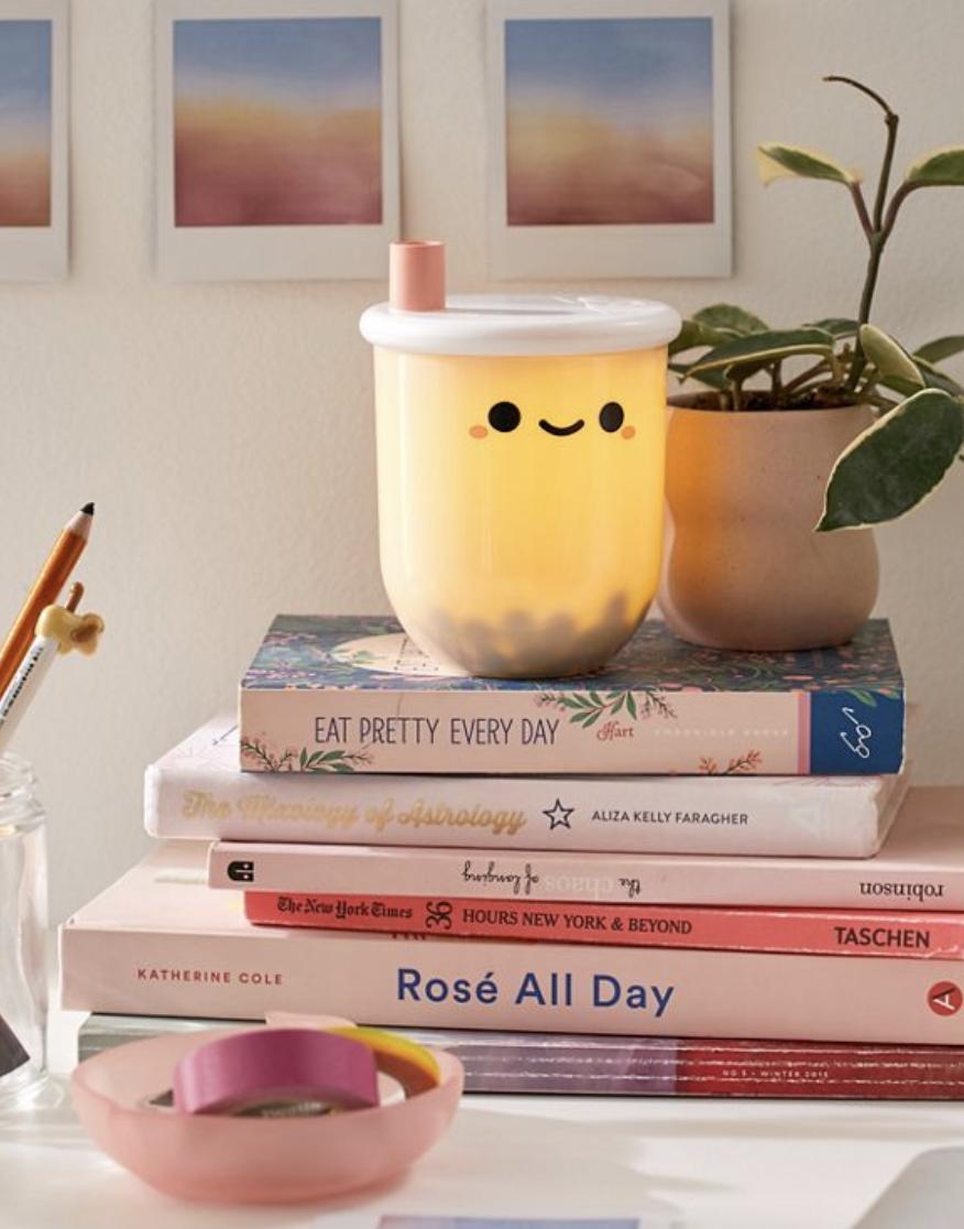 Boba tea-shaped mini lamp on colorful stack of books