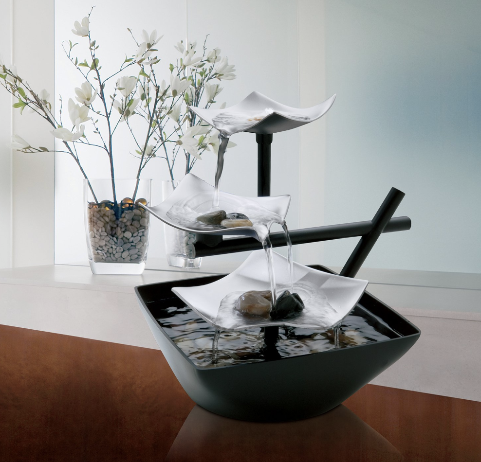 Black and silver indoor relaxation fountain with rocks and cascading water on top of a brown desk
