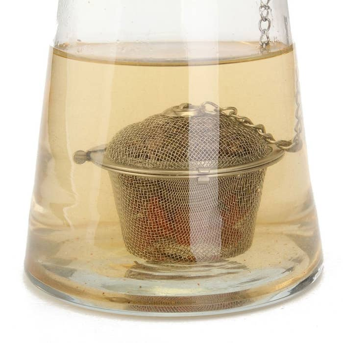 The tea infuser ball in a glass of water.