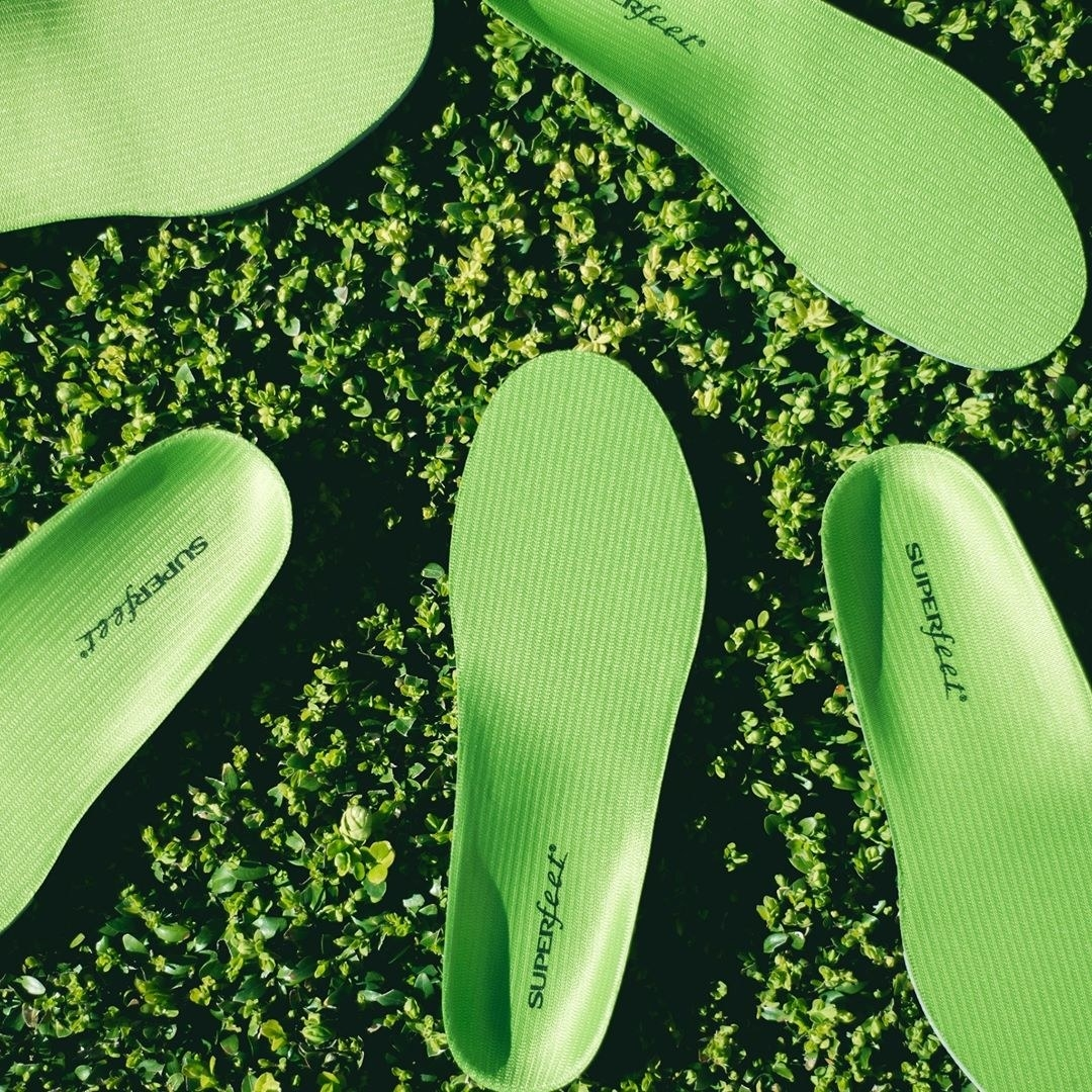 A pile of long shoe insoles lying on grass