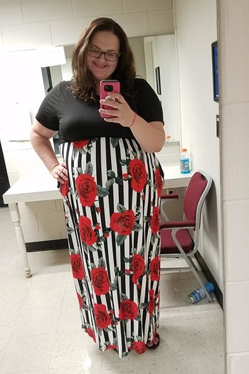reviewer wearing the dress with a solid top and floral and striped bottom