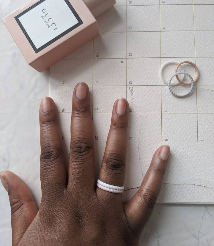 A person wearing two small silicone rings on their ring finger