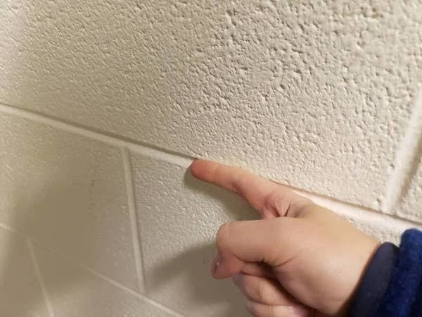 Picture of a person running their finger along a wall