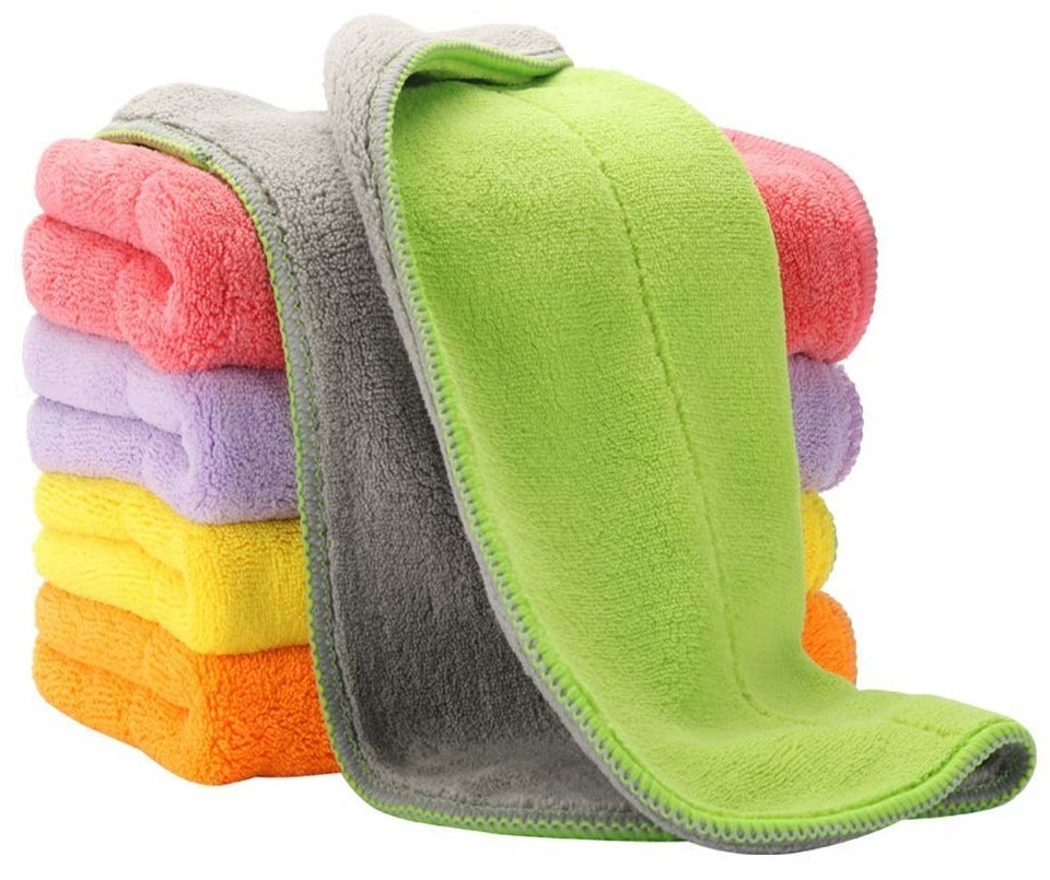 the stack of folded cleaning clothes in multiple colors