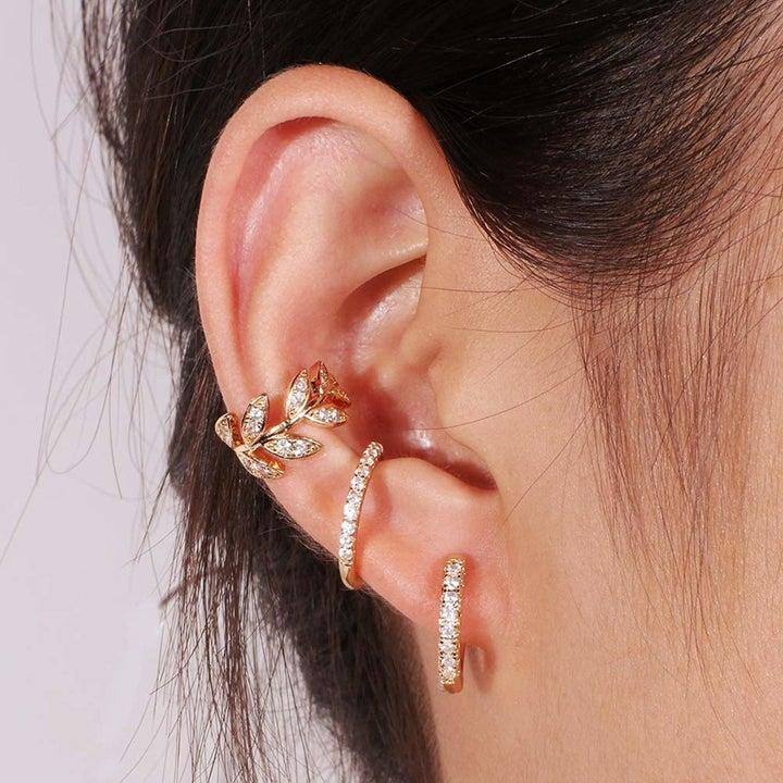 model wearing gold earring cuffs on ear