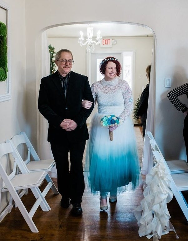 man walking bride down the aisle who's wearing a dress with a long-sleeved lace top with a pearl collar and a white-to-teal ombré tulle skirt