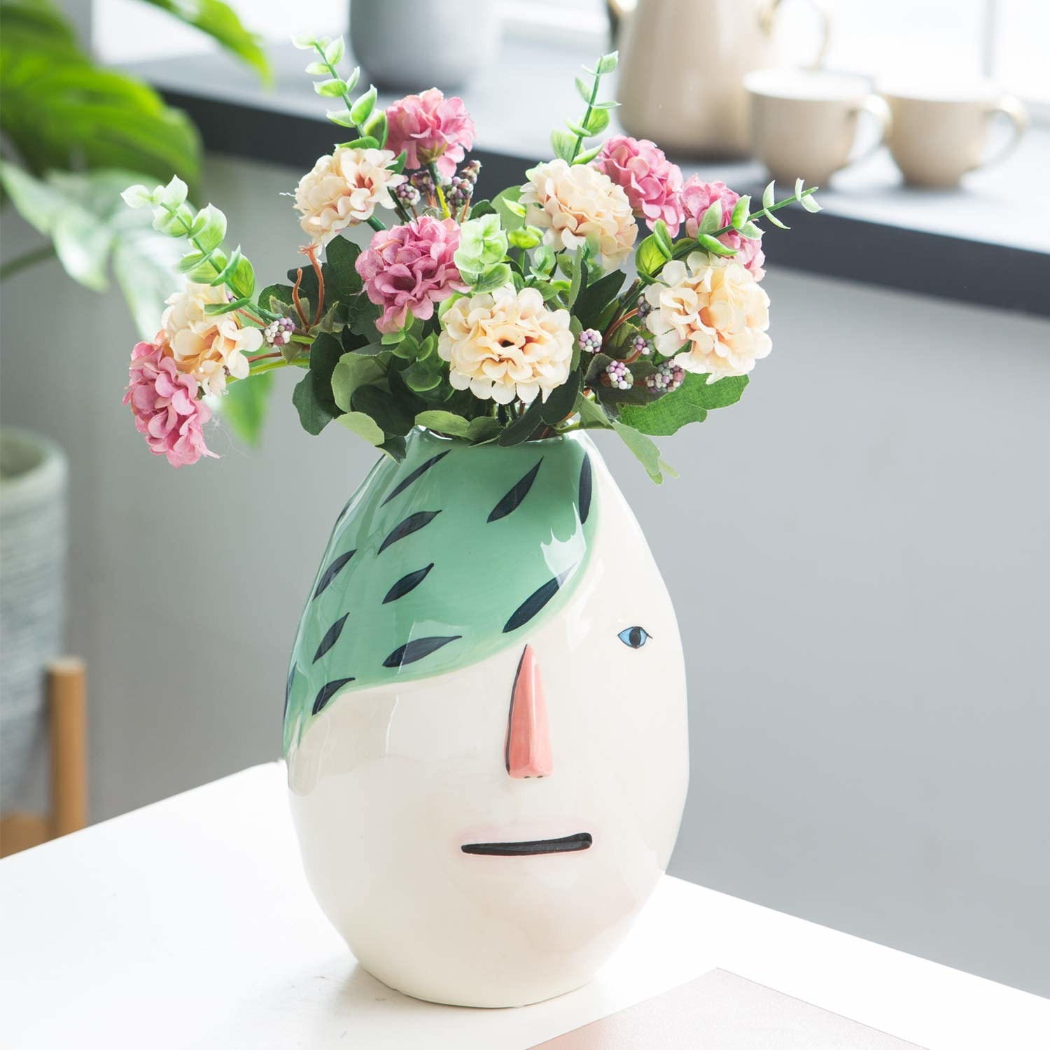 oval vase with face with green hair covering one eye