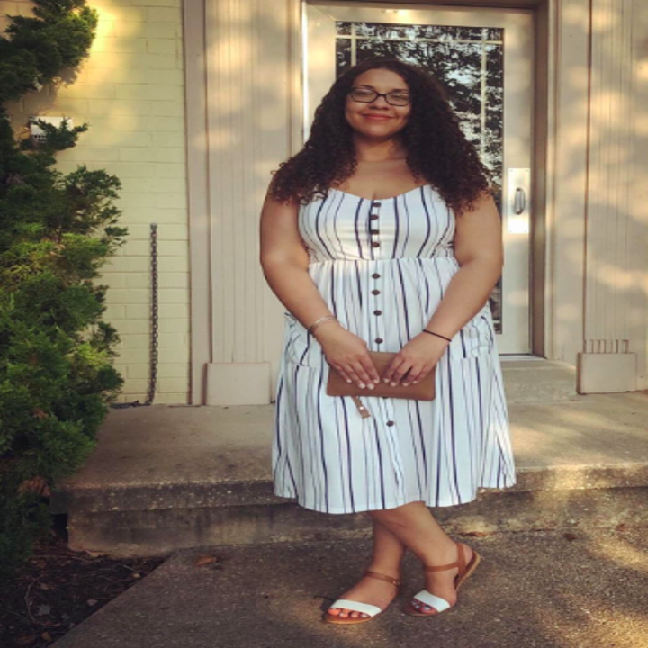 A reviewer in the spaghetti strap dress in white with vertical stripes