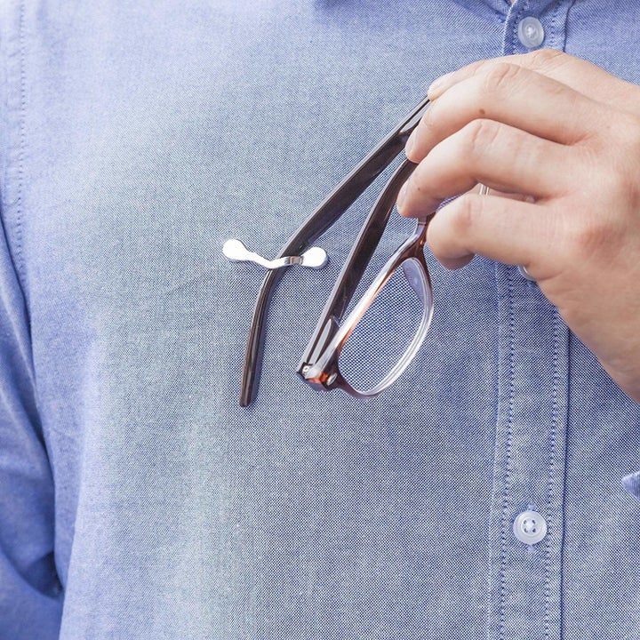 person putting their glasses on their readerest clip