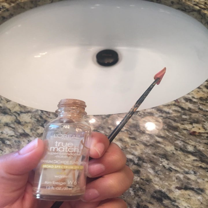 A reviewer holding a small spatula next to an empty makeup container