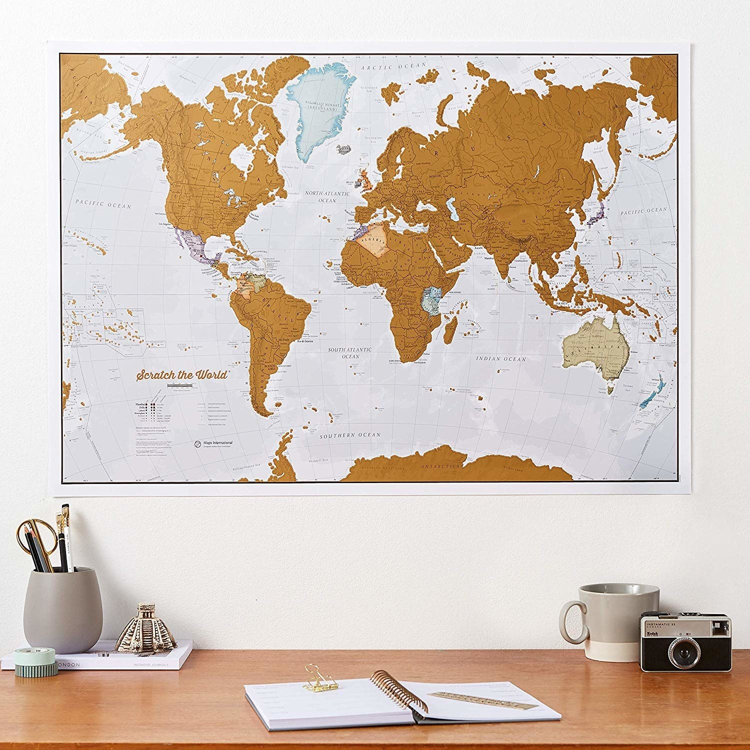 A large map of the world on a wall, with several countries scratched off