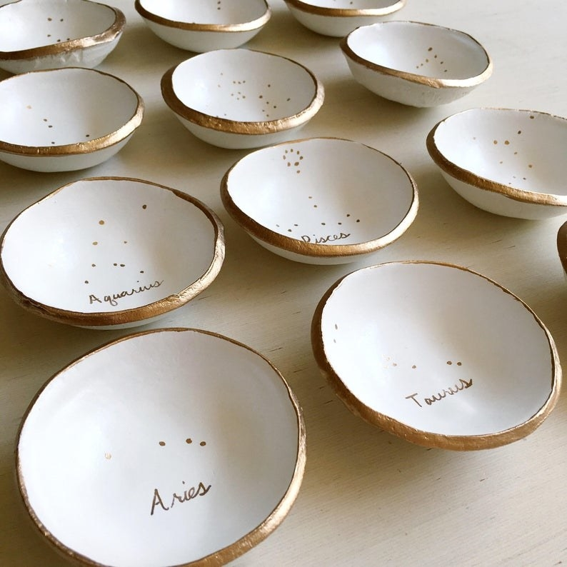 White jewelry dishes with gold rims and the zodiac sign scribed inside of it in matching gold.