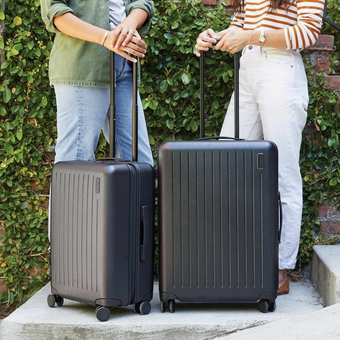 the two different sized Brandless suitcases in black
